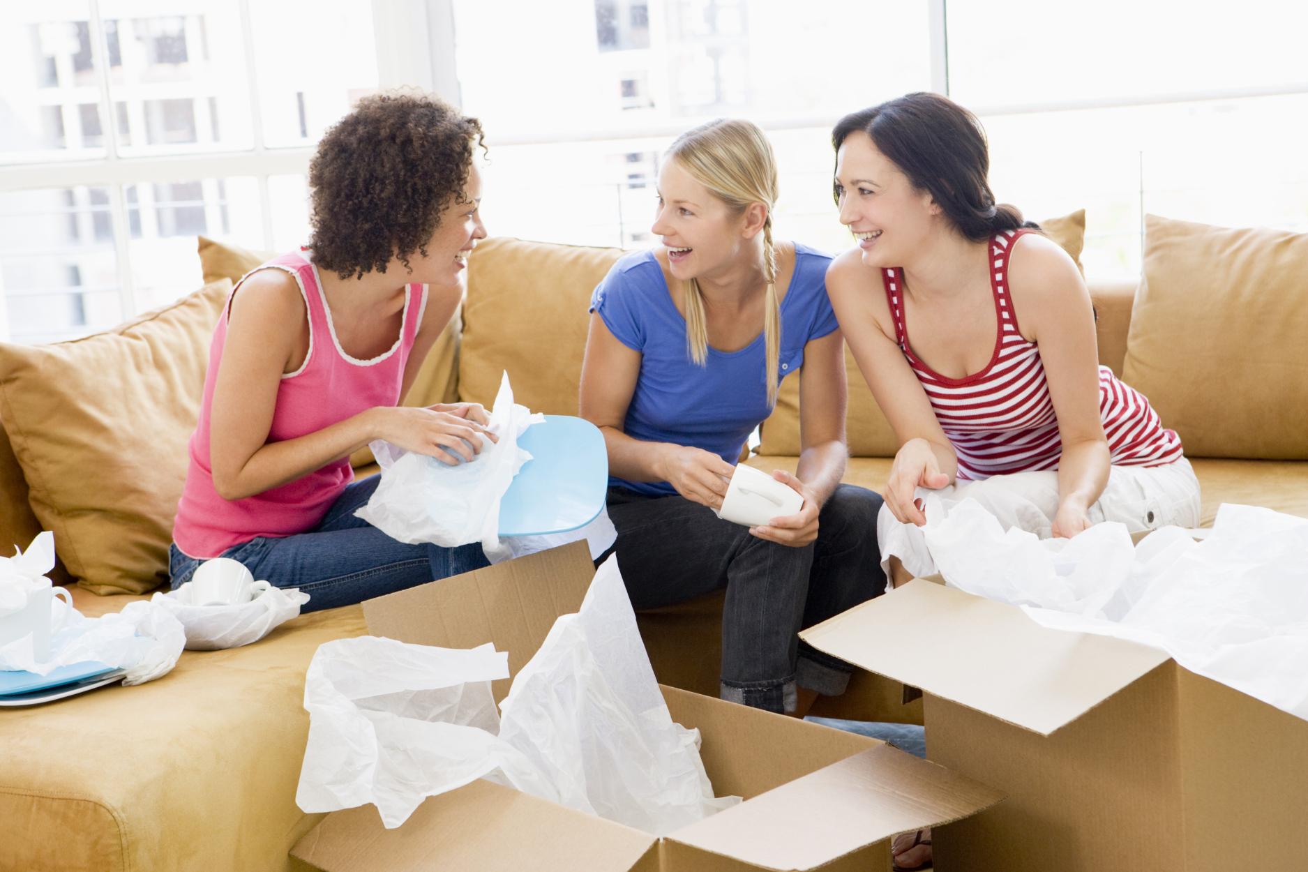 3 Frauen Packen Geschirr nach dem Umzug aus den Kartons